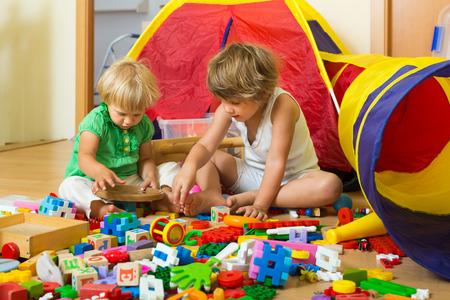 Niños tranquilos jugando con los juguetes en casa interior