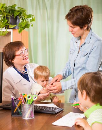 pediatra: Amistoso m�dico pediatra femenina examinar los ni�os Foto de archivo