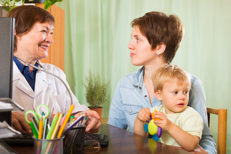 general pediatrician: Mature pediatrician doctor talking with mother of baby at clinic office