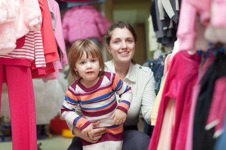 2 years: 2 years child with mother chooses wear at clothes shop. Focus on girl Stock Photo