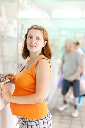 gravida: pregnant woman chooses drugs at the pharmacy drugstore