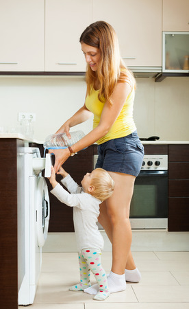 laundry detergent: Mother and child using washing machine with laundry detergent at home