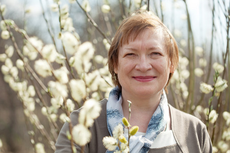 pussy willow: Smiling senior woman  in spring willow twig with buds outdoor Stock Photo