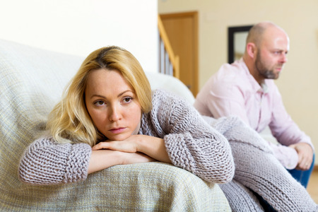 problem: Couple quarrel. Sad guy and wailful girl during quarrel  in living room at home couple having problems at home
