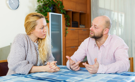 discussions: Serious  couple talking in home interior