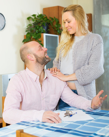 hypothec: Positive married couple sitting at table with keys and documents. Focus on man Stock Photo