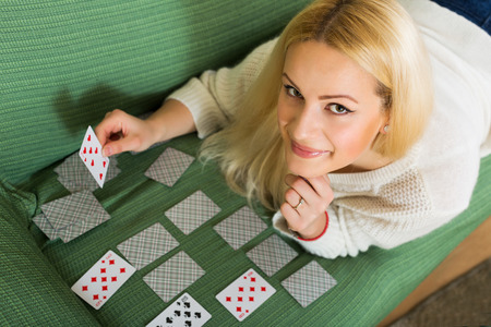 Relaxed positive housewife on couch telling fortunes by cards indoors