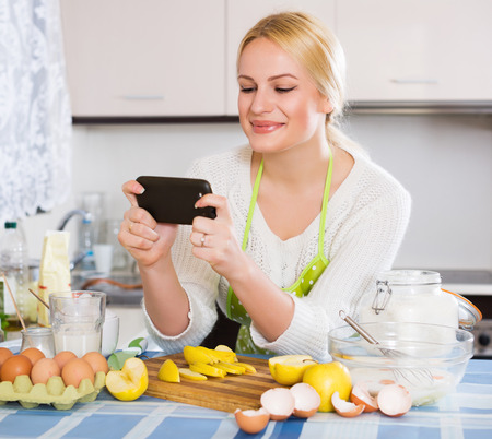 Smiling young woman with apples, eggs and phone doing selfie at kitchen photo