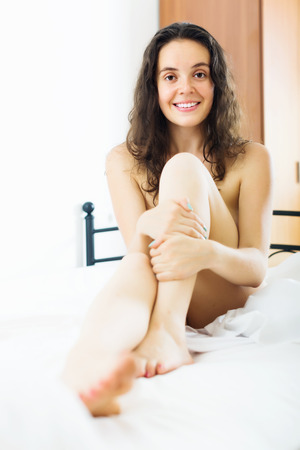 nudity: Happy nudity girl sitting on bed at bedroom