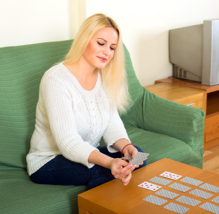 Thoughtful blond woman sitting on sofa at home and playing solitaire