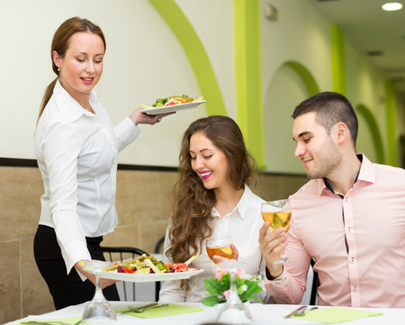 waiter: Female waiter with plates in hands serving guests table in restaurant. Focus on girl