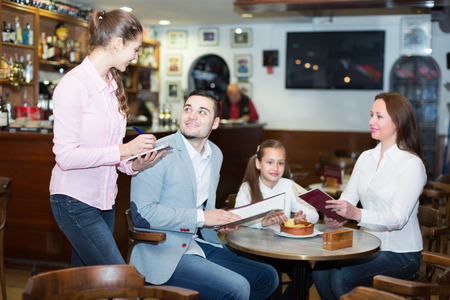 Cheerful waitress and happy family with child at cafe. Focus on weitress photo