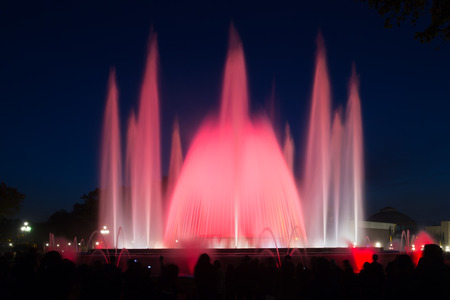 gazer: Evening view at colorful  fountain Montjuic show and people watching it nearby in Barcelona. Spain