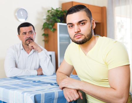 odds: Two serious male adults being at odds indoors Stock Photo