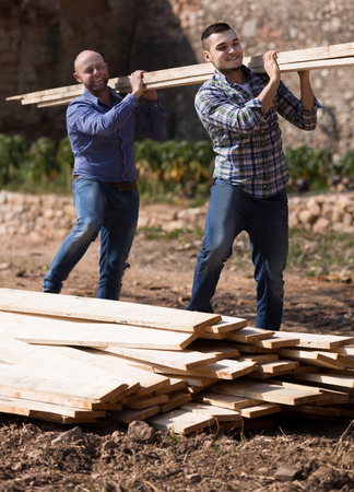 workmen: Happy russian workmen arranging building timber at farm Stock Photo
