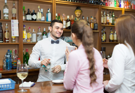 female friends chatting with handsome  barman and drinking wine in bar Stock Photo