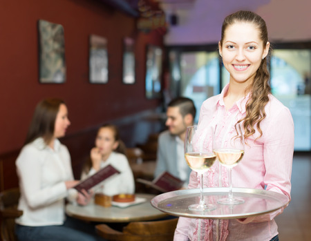 hospitality staff: Smiling nippy with beverages  on tray and bar crew at background