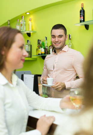 flirtation: Two beautiful female friends chatting and drinking wine at the bar