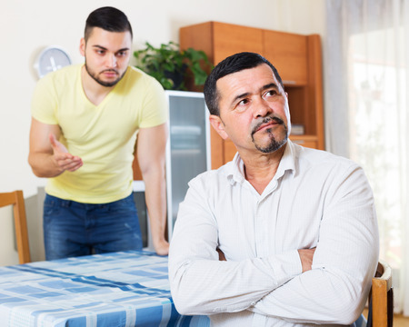 indoors: Men arguing about something indoors