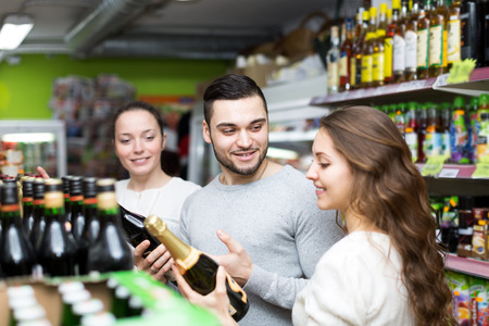 Three friends choosing champagne in a supermarket photo