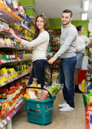 canned goods: american customers standing near shelves with canned goods at shop