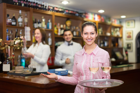 barmen: Smiling young nippy with beverages and bar crew at background