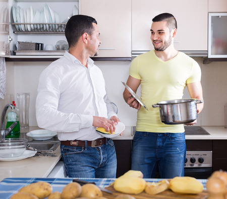 Two cheerful men cooking and doing dishes at home kitchen. Selective focus photo