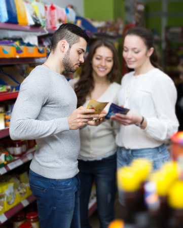 adult european customers standing near shelves with canned goods at shop photo