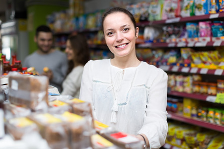 Young caucasian woman purchasing food for week at supermarket photo