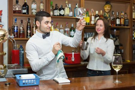 barmen: Positive waitress and smiling barmen working in modern bar. Focus on man