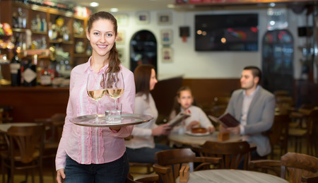 barmen: Smiling nippy with beverages and bar crew at background Stock Photo