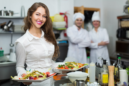 waitress: Smiling young waitress take dishes with food at  kitchen