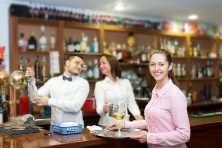 bartenders: Happy waitress holding tray with glasses, bartenders at the distance