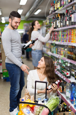Positive woman and  man  buying beverages for dinner at food shop photo