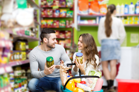 canned goods: Young smiling couple standing near shelves with canned goods at shop Stock Photo
