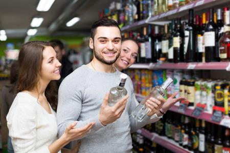 alcool: Enthousiaste acheteurs avec des bouteilles de vodka au supermarch�. Focus sur gars