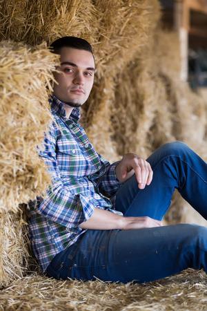 hayrick: farmer sitting on haystack at  shed Stock Photo