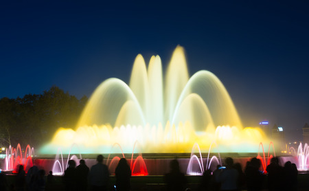 gazer: Evening view at colorful vocal fountain Montjuic show and people watching it nearby in Catalonia. Spain Stock Photo