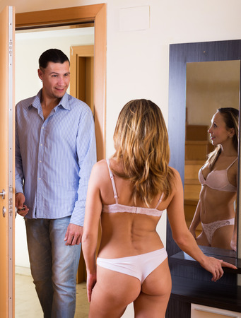 coming home: Young beautiful woman in the underwear and her boyfriend coming home