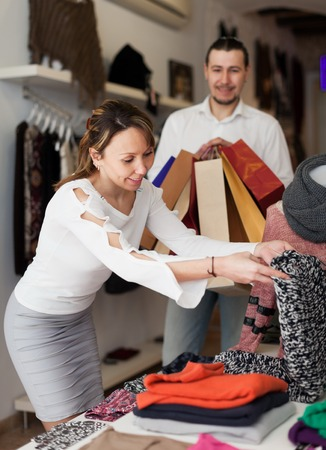 choosing clothes: Joyful adult couple choosing clothes at clothing shop Stock Photo