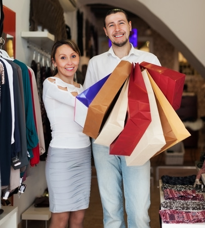 clothing store: Couple with shopping bags at clothing store together Stock Photo