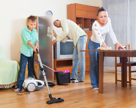 households: Adult couple with teenage son doing house cleaning at home