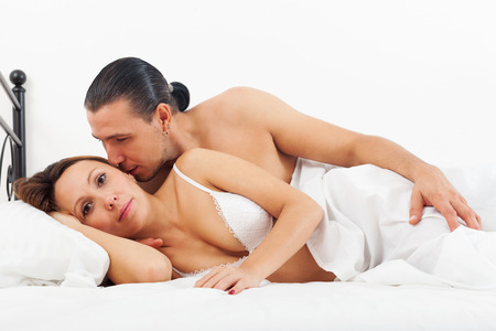 awaking: adult couple awaking together on bed in home interior