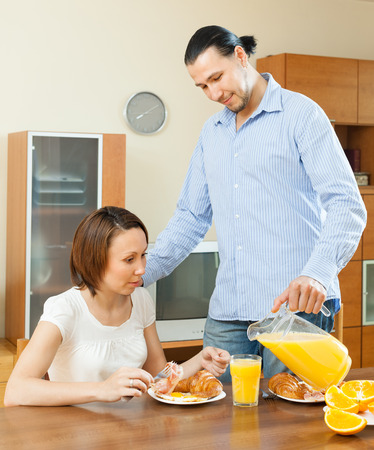 Happy adult couple having breakfast with juice in motning Stock Photo