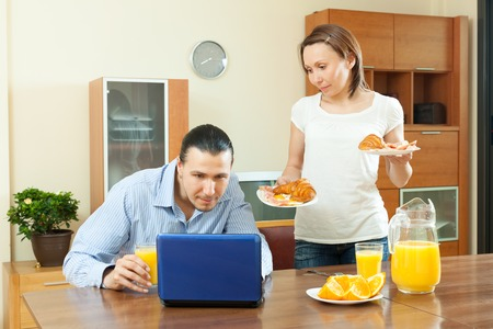 laptot: Man using laptot, pretty wife serves morning breakfast her husband man at home Stock Photo
