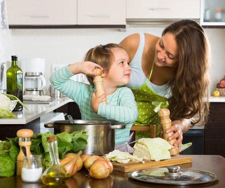 cook house: Young mother with little daughter cooking at home kitchen
