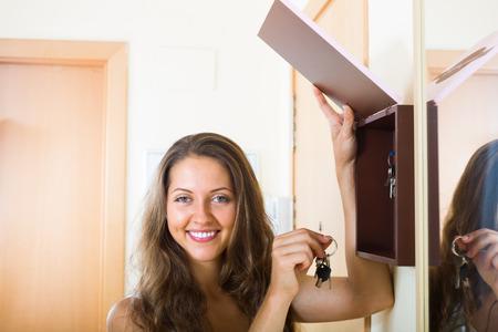 housekeeper: Muchacha sonriente feliz con el manojo de llaves que permanezcan cerca de ama de llaves Foto de archivo