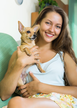 russkiy: Smiling girl holding Russkiy Toy Terrier at home