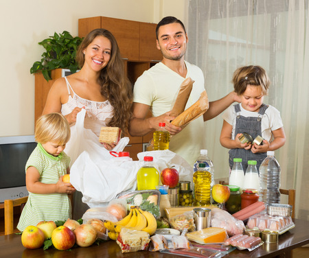 purchased: Smiling young parents with female children sorting purchased food out indoor