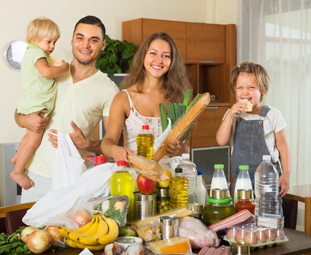 sorting out: Positive family with little children sorting purchased food out indoor Stock Photo